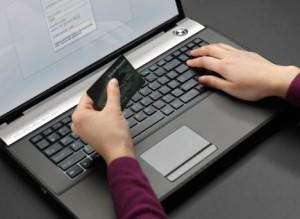 Woman sitting at a laptop and entering her credit card information into an online form